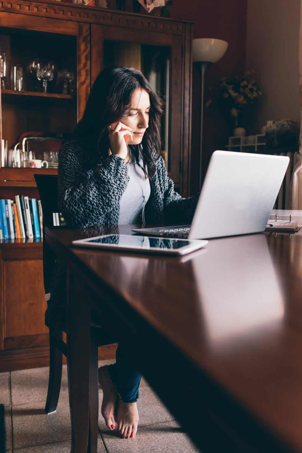 Entrepreneur calling on phone and working on line with a laptop sitting in a desk at home - business, technology, multitasking concept